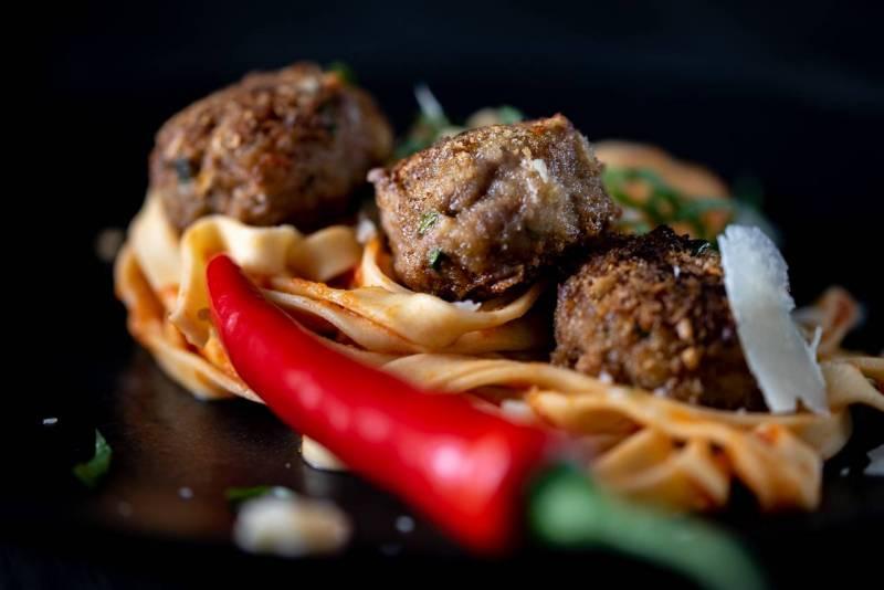 Nahaufnahme: Tagliatelle mit Fleischbälchen und einer roten Chilli auf schwarzem Teller auf schwarzem Holzuntergrund (Foto: Thomas Vonier)