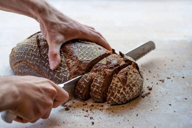 """München, Maxvorstadt 2019   Brotlaib wird mit Messer aufgeschnitten.Julius Brantner betreibt seit 2019 die gläsern Backstube """"Brothandwerk"""". Der 27-jährige gibt seinen Kunden die Möglichkeit ihm bei der Arbeit und dem Brot bei der Entstehung zuzuschaun. Alle Arbeitsschritte sind einsehbar. Er sagt, ich habe nichts zu verbergen und möchte perfektes ehrliches Brot anbieten."""