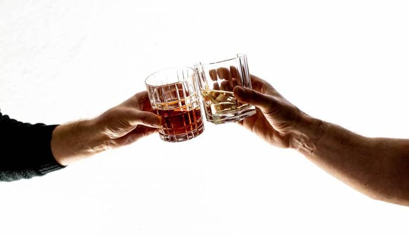 Zwei Hände mit Whiskeygläsern prosten sich zu.